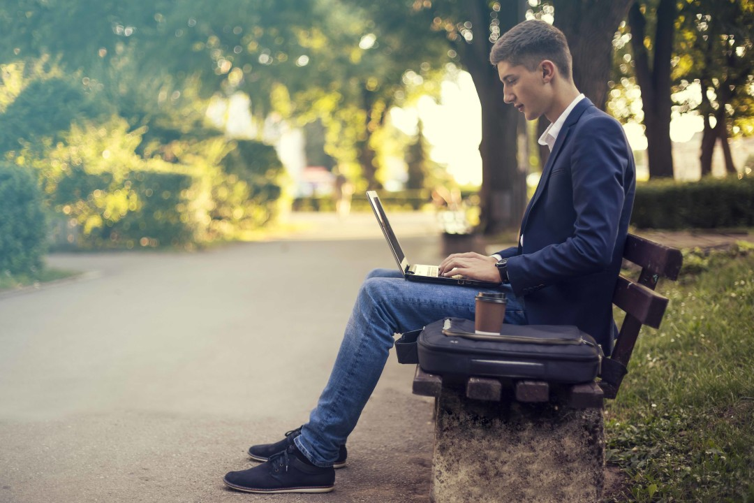 Businessman working on a laptop in a park