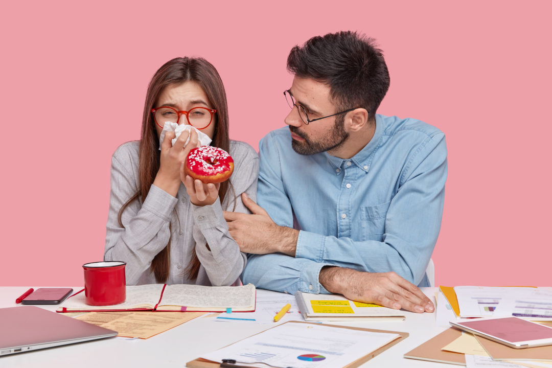 Stop crying please. Upset bearded young man in formal shirt, calms dejected woman who uses tissue, eats delicious doughnut, work with documentation, pose together against pink studio background